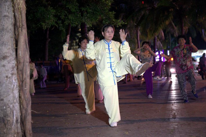 Жители города Санья занимаются ушу вечером на набережной